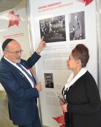 Rabbi Reuven Bulka and Sharon Gray - Shlozberg at the opening of the CJE Exhibition showing the CJE Serving Democracy panel. Rabbi Bulka is pointing to a photo of the Late Rt. Hon. Herb Gray flanked by Prime Ministers Jean Chretien and  PaulMartin in House of Commons. Other photos show Henry Nathan the first Jew elected to the Canadian House of Commons in 1871.  Below is David Lewis the first Jewish leader of a Canadian political party, the New Democratic Party.